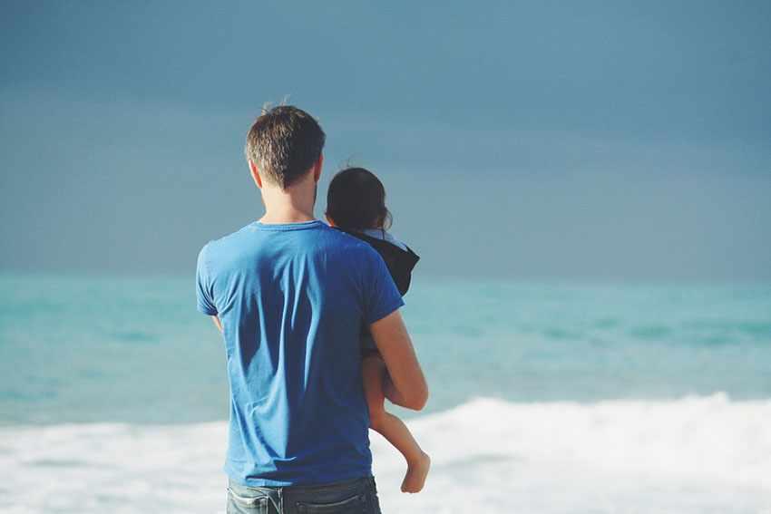 отец держит в руках ребенка на берегу океана