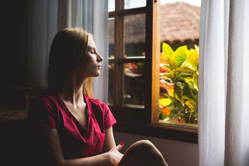 медитирует возле окна