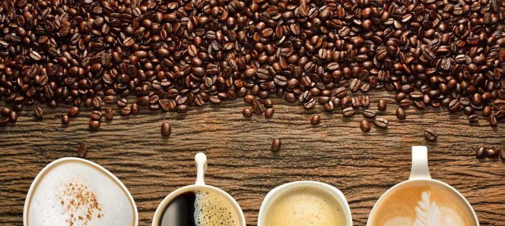Кофейные зерна и чашки с разными видами кофе
