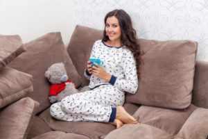 Девушка в пижаме сидит на диване с чашкой