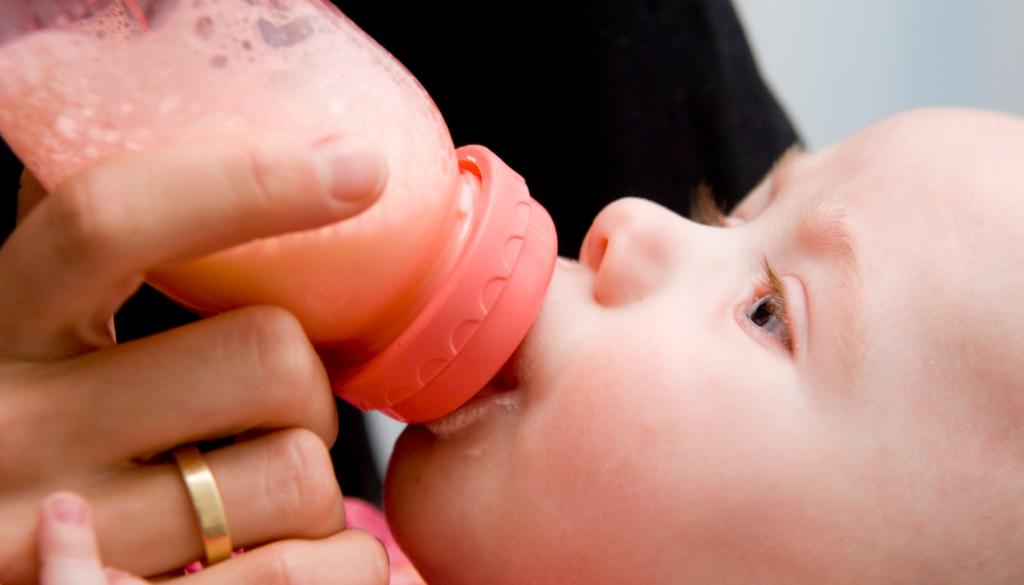 Ребенок ест кашу из бутылочки.